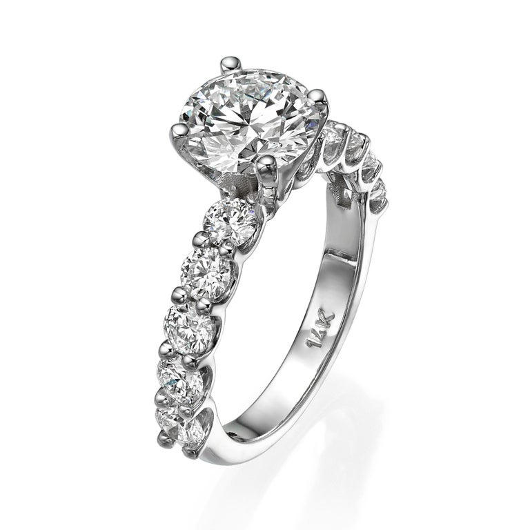 Our handcrafted timeless engagement ring is set with 1.77 Carat round brilliant cut GIA certified diamond G/ VVS1  and surrounded by 10 round brilliant cut diamonds 1.20 Carat total weight D-E / VVS.  Our high quality diamonds are mounted on 14K
