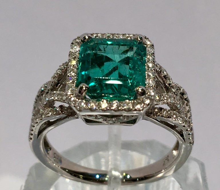 Octagonal, step cut, natural beryl, Columbian emerald is prong set in 14 karat white gold and enhanced by a rectangular halo of round brilliant diamonds and diamond micro-pave details on the shank and the basket.  Underside of basket features a