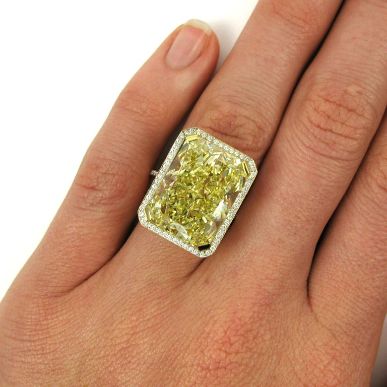 This incredible ring features a mega-sized 18.13 carat radiant-cut diamond with Fancy Yellow color and SI2 clarity. This one-of-a-kind stone is set into a dainty 18k yellow gold frame ring completely covered with white diamond pave.   Purchase