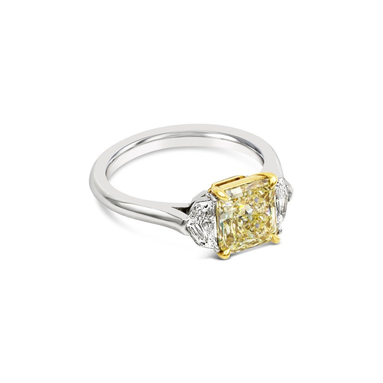 A gorgeous 2.01 carat radiant cut yellow diamond that GIA certified as Y-Z color, VS1 clarity, takes center stage in this three stone engagement ring. Flanking the center diamond are two shield cut diamonds weighing 0.47 carats total. Set in a 18k