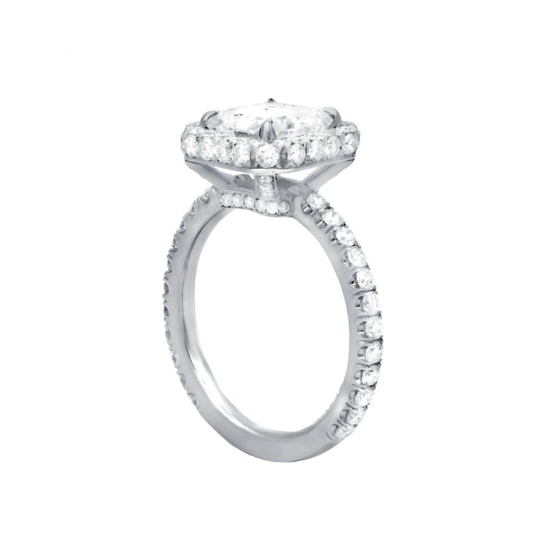 Fanciful and feminine diamond engagement ring in platinum mounting.The Main GIA certified emerald cut diamond features 2.01 cts G color/VVS1 clarity set in beautiful and custom made halo mounting with additional 1.35 cts round diamonds on the side.