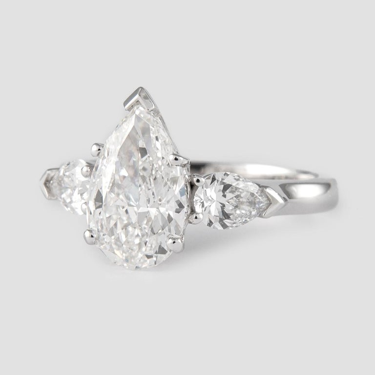 Stunning and classic three-stone diamond engagement ring, GIA certified. Center stone, 2.01ct pear cut diamond. G color grade, SI1 clarity grade, GIA certified. Side stones, 2 pear cut diamonds, approximately G color grade, SI1 clarity grade. 2.61ct