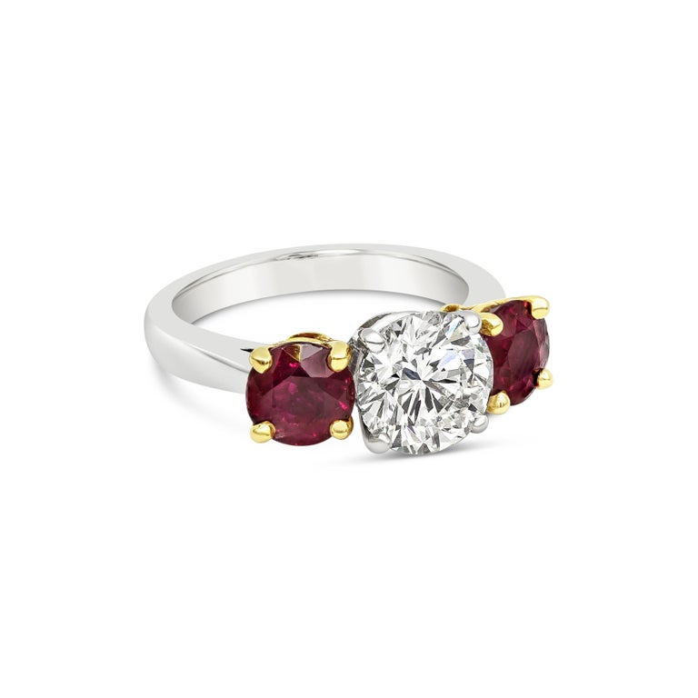A chic three-stone engagement ring style featuring a 2.04 carat round brilliant diamond certified by GIA as J color, VS2 clarity. Flanking the center diamond are color-rich round rubies weighing 2.14 carats total. Set in a polished platinum