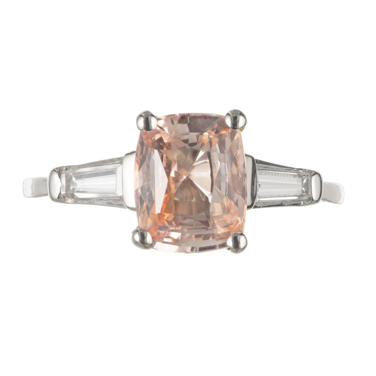 Orange Sapphire and diamond three-stone engagement ring. GIA certified cushion cut center sapphire with two tapered baguette side diamonds in a three-stone platinum setting. circa 1940's. Simple heat only, no other enhancements.  1 cushion cut