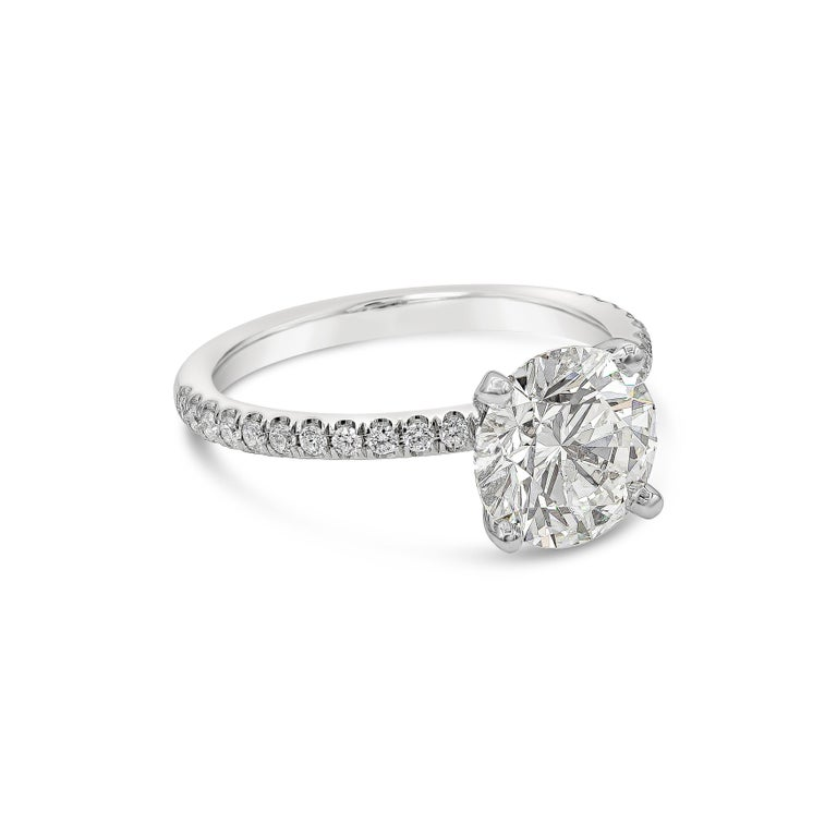 A classic pave engagement ring style showcasing a 2.10 carat round brilliant diamond, certified by GIA as G color, SI2 clarity. Set in a diamond encrusted shank made in 18k white gold. Accent diamonds weigh 0.20 carats total.   Style available in