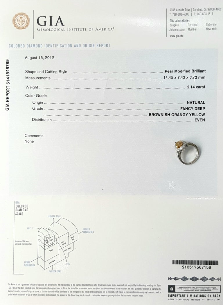This GIA certified 2.12 Carat Fancy Yellow Diamond is set in Platinum with accenting diamond set on the halo and down the sides.The gallery on the sides is detailed with minimal swirl designs alongside a touch of milgrain giving it a vintage twist