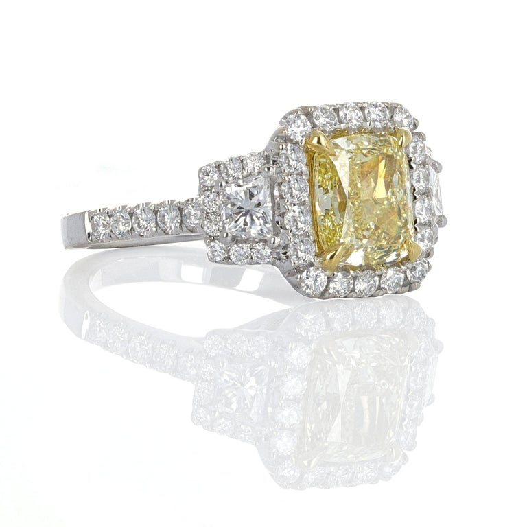 Three stone, GIA certified, Fancy Light Yellow cushion cut diamond ring. The center stone weighs 2.20 carats. The side stones, including the pave, weigh 1.14 carats. GIA describes the center stone as a natural cushion modified brilliant cut diamond.