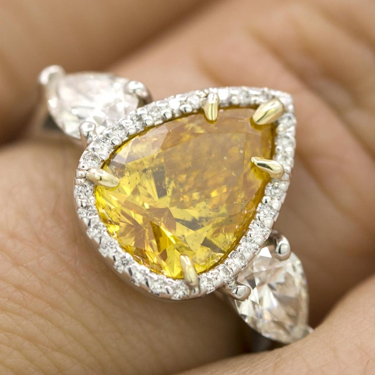 This GIA certified 2.20 ct  Vivid Yellow-Orange Pear Shaped Diamond is truly unique. The brilliance and brightness of the yellow color, combined with the warmth of the orange color make this diamond uniquely beautiful. GIA report 2145808831 states