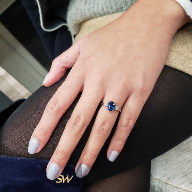 Features a gorgeous 2.38 carat oval cut natural sapphire that GIA certified as Blue in color with no indications of heating on the stone. Flanked by a bullet cut diamond side stone and each side weighing 0.29 carats total. Set in platinum.  Style