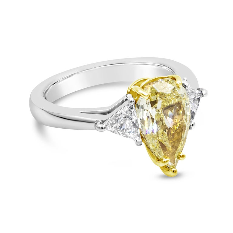 Showcasing a 2.45 carat natural pear shape yellow diamond flanked by a brilliant trillion diamond on either side. Accent diamonds weigh 0.47 carats. Set in a polished platinum mounting. GIA certified the center diamond as fancy light yellow in