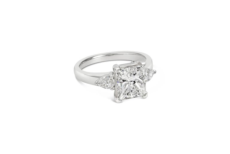 A beautiful engagement ring style showcasing a brilliant princess cut diamond certified by GIA as F color, VS2 clarity. Flanking the center diamond are brilliant pear shape diamonds weighing 0.40 carats total. Set in an everlasting platinum