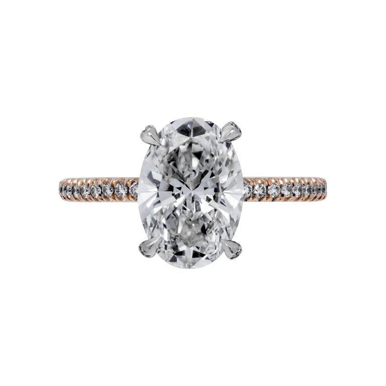 Timeless Classic, Oval Diamond Engagement  Mounted two tone metal -  14K Rose & White Gold, featuring exceptional pave work that compliments the center stone, Mounting features round brilliant cut diamonds in the basket under the stone - fully