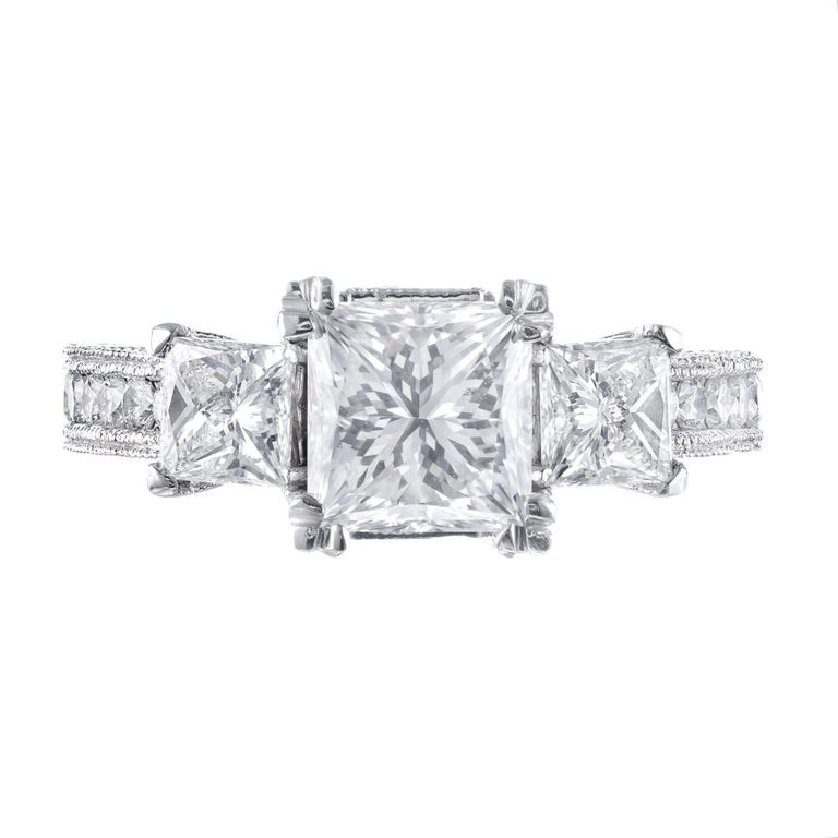 Three-stone diamond engagement ring. Square cut GIA certified center stone with two square cut accent diamonds accented with 32 round brilliant cut diamonds in a Platinum, three-stone bead setting.   1 square modified brilliant cut diamond, G VVS2