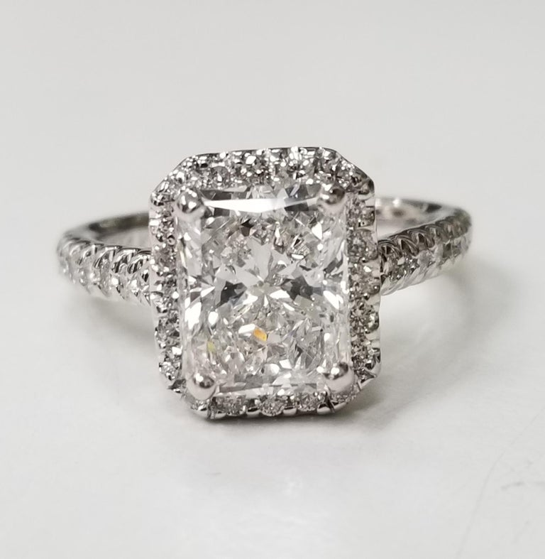 14k white gold diamond engagement ring, containing 1 radiant cut diamond; color