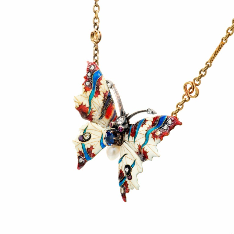 Diamond, pearl and sapphire butterfly pendant necklace. GIA certified natural no heat blue sapphire accented with natural peal, genuine ruby and old mine cut diamond accents. White, blue and red enamel. 17 inches long. Natural patina on this