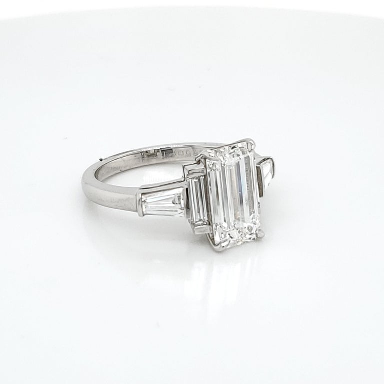 GIA Certified 3.02 Emerald Cut Diamond Five Stone Ring. The center stone is GIA certified G Color VS1 clarity. On the side of the 3.02 Emerald Cut Diamond are 2 very long shaped emerald cut diamonds followed by two  step cut tapered baguettes. The