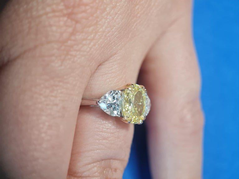An exquisite Antinori Fine Jewels creation. A 3.05 carat fancy yellow oval diamond solitaire with an extremely bright and even fancy yellow color.  The side diamonds are internally flawless d color triple excellent none fluorescence investment grade