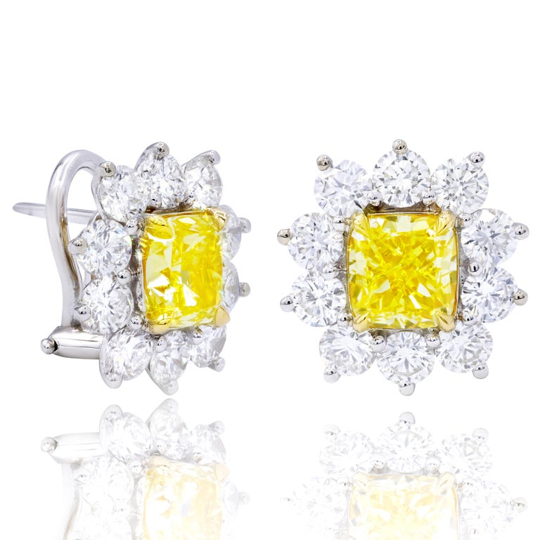 This Beautiful 18kt Yellow and white Gold diamond Earrings features Cushion Cut 1.55 Carats Fancy Light Yellow, VVS2 GIA #6272622866 and Cushion Cut 1.51 carats Fancy light yellow VS1 GIA#6242169214 surrounded by 1.60 carats of large round brilliant
