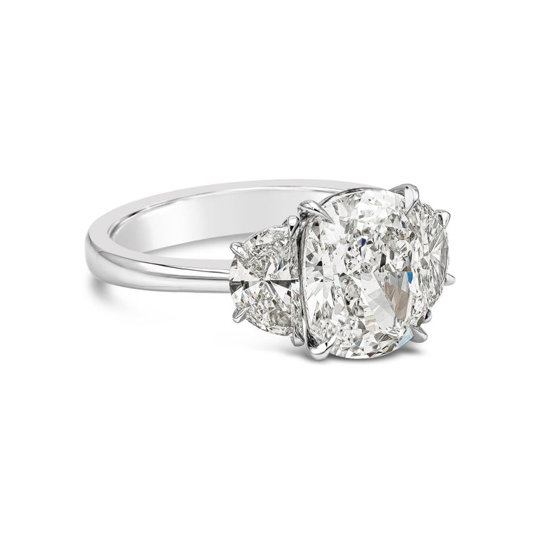 Showcasing a brilliant cushion cut diamond weighing 3.11 carats, accented by two brilliant half moon diamonds weighing 0.90 carats total. Set in a polished platinum mounting. Accompanied by a GIA report certifying the center diamond as H color, SI1