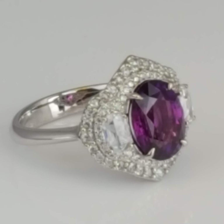 (DiamondTown) With a GIA Certified 3.31 carat oval cut purple sapphire center, and 0.70 carats white diamonds, this ring shines from every angle. Intricate hand engraved milgrain work throughout adds to the charm of the piece.  GIA Certification