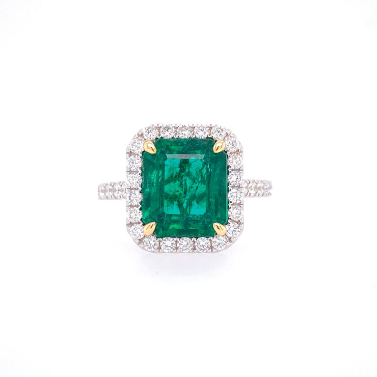 This stunning Cocktail Ring features a beautiful GIA Certified 3.80 Carat Emerald Cut Emerald with a Diamond Halo, that sits on a Diamond Shank. This Ring is set in 18K White Gold, with 18K Yellow Gold prongs on the center stone.  Total Diamond
