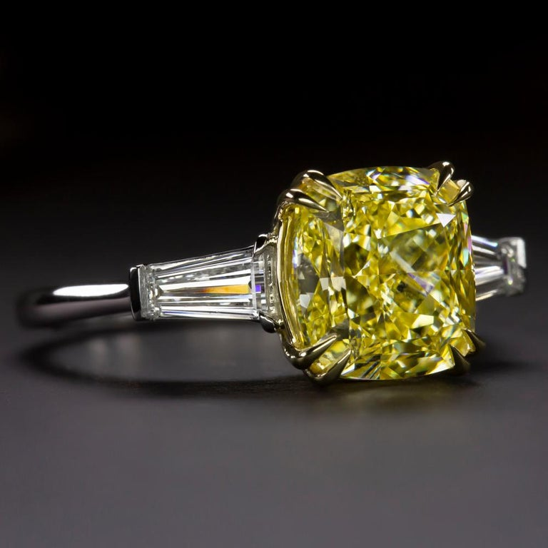 An exquisite GIA certified fancy intense yellow cushion cut diamond ring with two side tapered baguette natural diamonds at each side mounted in 18 carats yellow gold and platinum.  The main stone has a strong yellow. The stone has an intense color