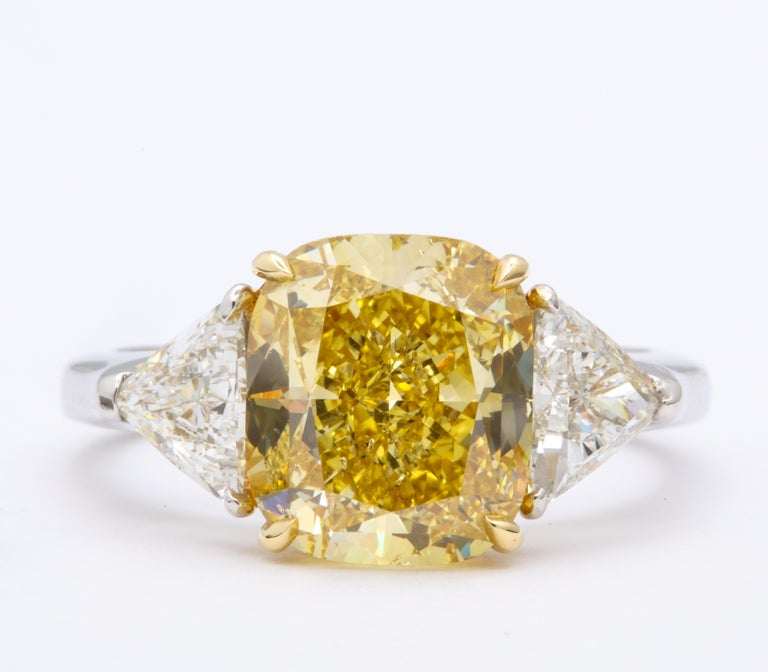 Stunning cushion cut 4.30 carat GIA certified Fancy Intense Yellow diamond, SI2.   Set with 1.10 carats of white trillion cut side diamonds.   Platinum and 18k yellow  Currently a size 6, this ring can easily be sized.   Pictures do not do this