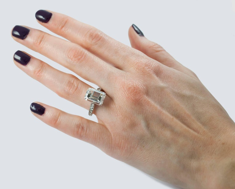 This solitaire ring features a GIA certified emerald cut diamond that weighs 4.11 carats and is graded with I color and VS1 clarity. It is mounted on a platinum band with pave diamonds down each side and etching details all around the