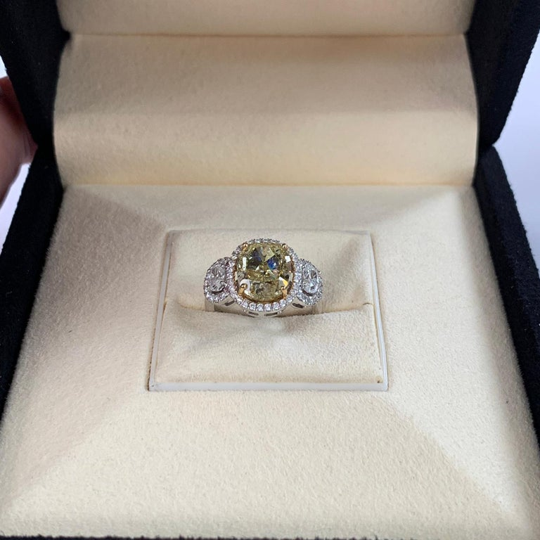 Natural fancy yellow cushion cut diamond weighing 4.01 carats. Certified by GIA. beautifully accompany by 2 oval diamonds and set in 4 prong halo setting. Its transparency and luster are excellent. 18K white gold, this fancy yellow cushion shape