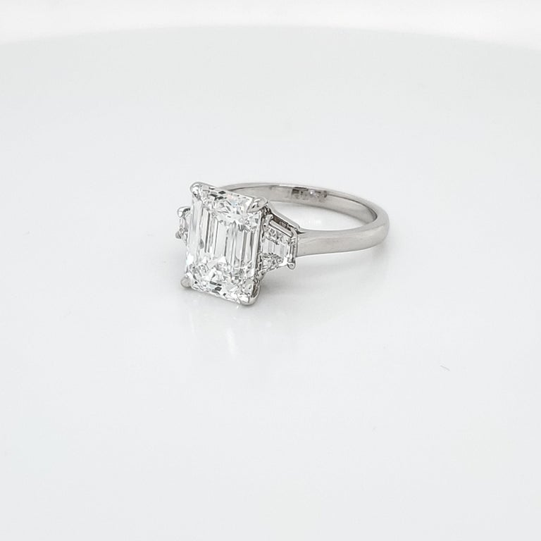 GIA Certified 4.02 carat Emerald Cut Three Stone Ring set in platinum with 2 trapezoid shaped diamonds weighing 0.64 carat total. This is a perfect Emerald Cut. 1.34 Length to Width Ratio, not to square, not to rectangle. D color and VS2 clarity,