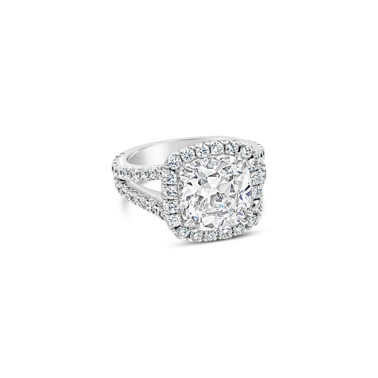 Features a 4.11 carat cushion cut diamond certified by GIA as G color, SI1 clarity, surrounded by a single row of round brilliant diamonds. Set on an accented split-shank band made in 18 karat white gold. Accent diamonds weigh 1.40 carats total.