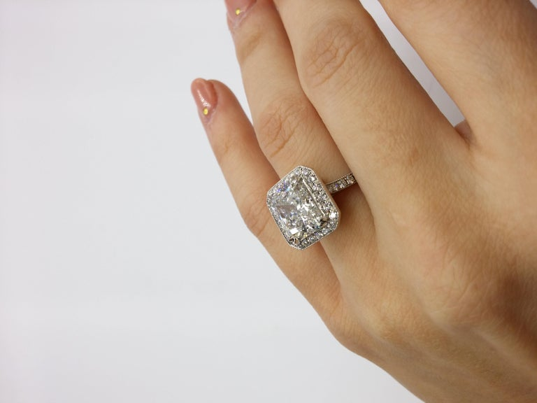 Platinum diamond ring, features 4.18 Carat Radiant in the center surrounded by 0.70 Carats of diamonds around.