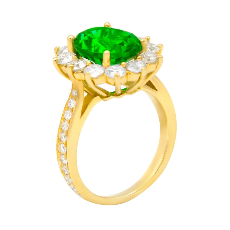 18K Yellow Gold vibrant green emerald ring.  The cneter stone is 4.20 Carat Oval Shaped Green emerald, surrounded by 1.80 Carats of round brilliant cut diamonds. set in yellow gold.