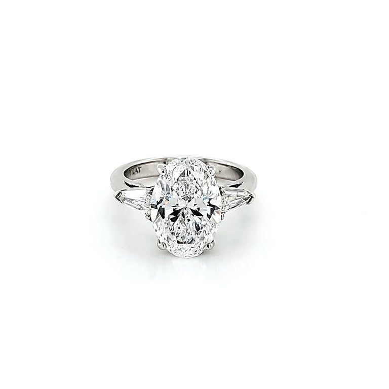 Center stone is a GIA certified 4.23 carat Oval Diamond D color VS2 clarity. Set in a handmade platinum ring with 2 bullet shaped side stone diamonds weighing 0.47 carats, This ring can be changed to a ring of your choice if interested. All our