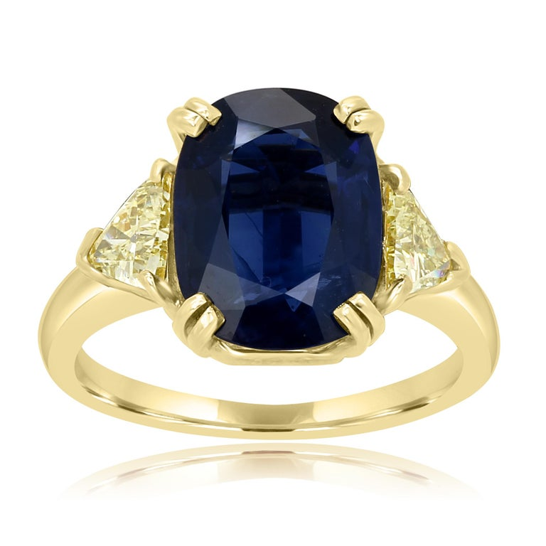 GIA Certified 4.39 Carat Blue Sapphire Cushion Flanked by 2 Fancy Yellow Diamond Trillions 0.50 Carat on the side in 18K Yellow Gold Three Stone Classic Ring.  MADE IN USA Center Blue Sapphire Cushion Weight 4.39 Carat Total Weight 4.89 Carat