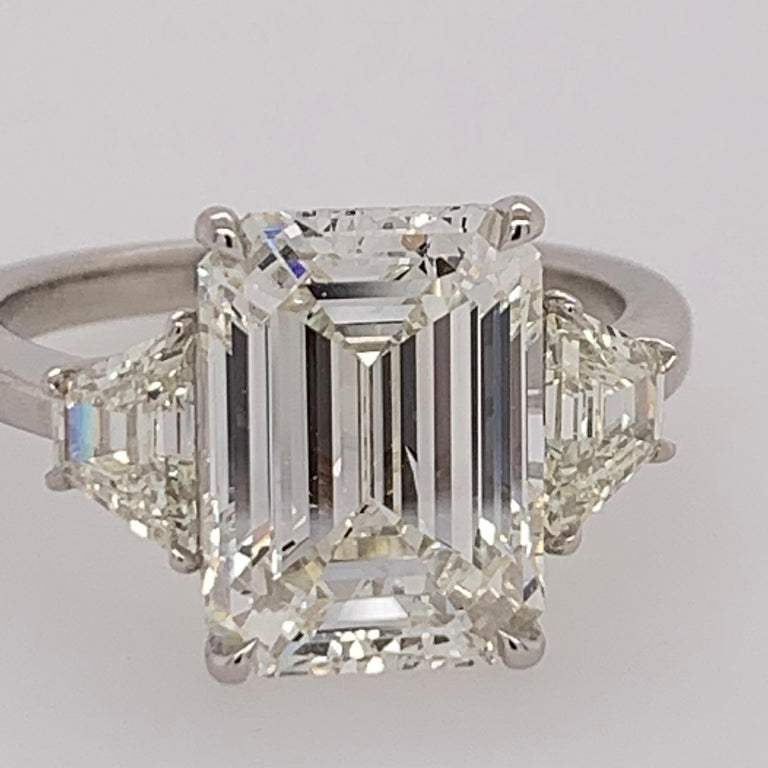 A stunning Platinum & Natural Diamond Engagement Ring. The centerstone is a 4.40 carat rectangular shaped emerald cut, GIA certified as a J in color and VS2 vs2 in clarity. The color and clarity are very pleasant, and the measurements of