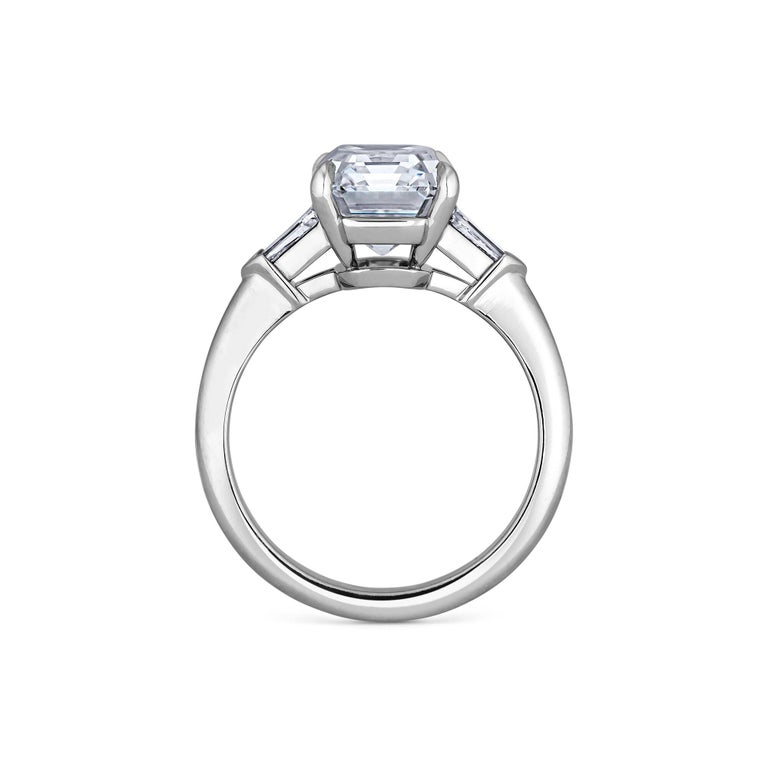 This quintessentially elegant 4.42 carat emerald cut diamond engagement ring will quickly become a girls best friend. Luxuriously set in a handmade mounting with four prongs and side bullet cut diamonds, this extraordinary ring will take your