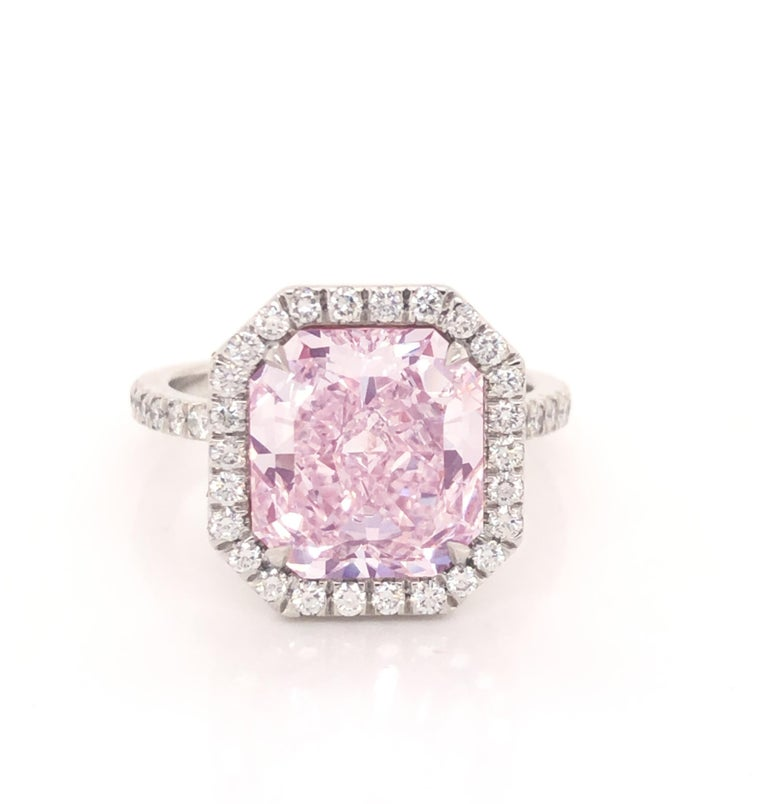 Beautiful hand made ring crafted in platinum by master jewelers. The focal point of the ring is one of the rarest diamonds in the world. A natural pink diamond. The center stone is one radiant cut diamond. Accompanied by a GIA certificate, the
