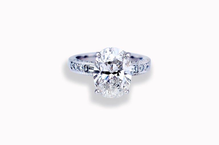 This oval diamond engagement ring has all the looks of the most popular engagement ring design currently.  The center diamond is GIA certified with 10378029.  The center stone is H color and VS2 clarity.  The measurements are 12.43 x 9.09 x 5.92 mm.