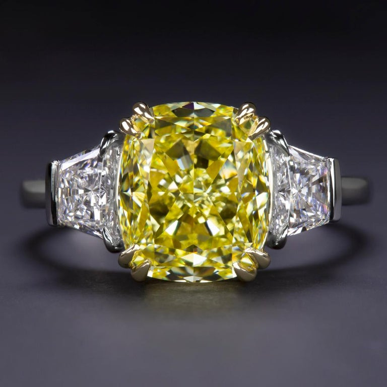 This Beautiful Classic engagement ring from Antinori Fine Jewels features an over 3.53 carat fancy vivid yellow radiant cut diamond with GIA certificate flanked by trapezoid pure diamonds.  The mounting is platinum and 18 karats Yellow Gold. Truly