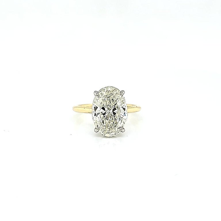 GIA certified Oval Diamond, L color, SI2 clarity. Set in a ultra thin 18k yellow Gold and Platinum ring. Can be restyled any way you like or ask us about many other diamond options we have available. Ring is size 6.5 but can be sized as needed.