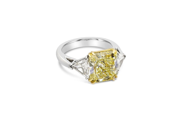 This three-stone engagement ring features a 4.50 carat radiant cut yellow diamond, certified by GIA as Fancy Yellow color, VS1 clarity. Flanking the center diamond are brilliant trillion cut diamonds weighing 0.50 carats each. Set in a polished