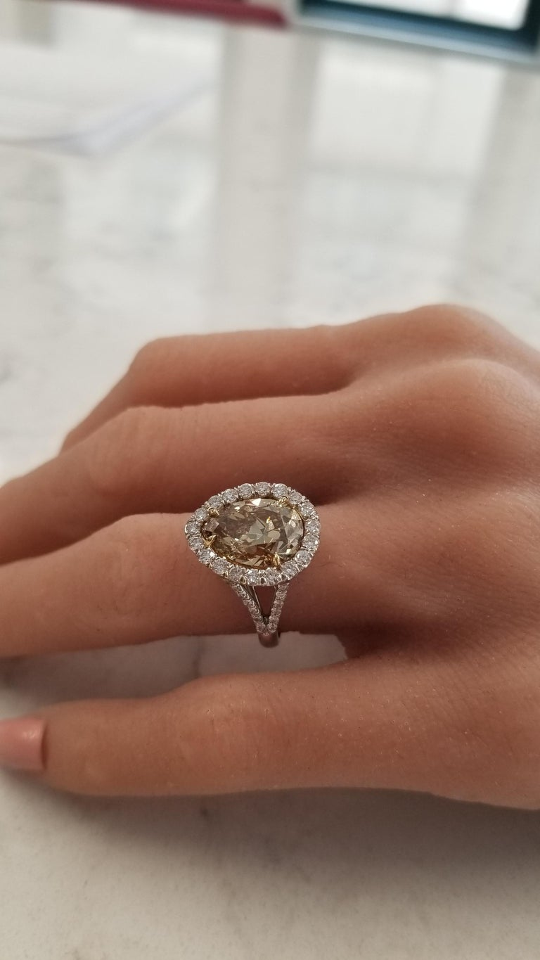Designed with luxury and vibrancy, this ring showcases a GIA certified 4.68 carat fancy brown-yellow diamond with measurements of 12.42-8.84mm, in a double prong rich yellow gold setting. This natural colored diamond is VS2 in clarity and has an