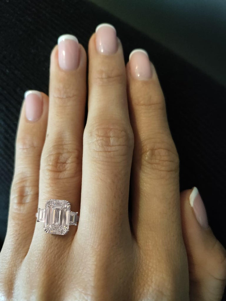 Platinum three stone emerald cut diamond engagement ring. Centering one fine quality emerald cut diamond weighing 6.25 carats. Flanked by two trapezoid cut diamonds weighing a combined total of 0.75 carats.  Diamond grading: color grade: J. Clarity