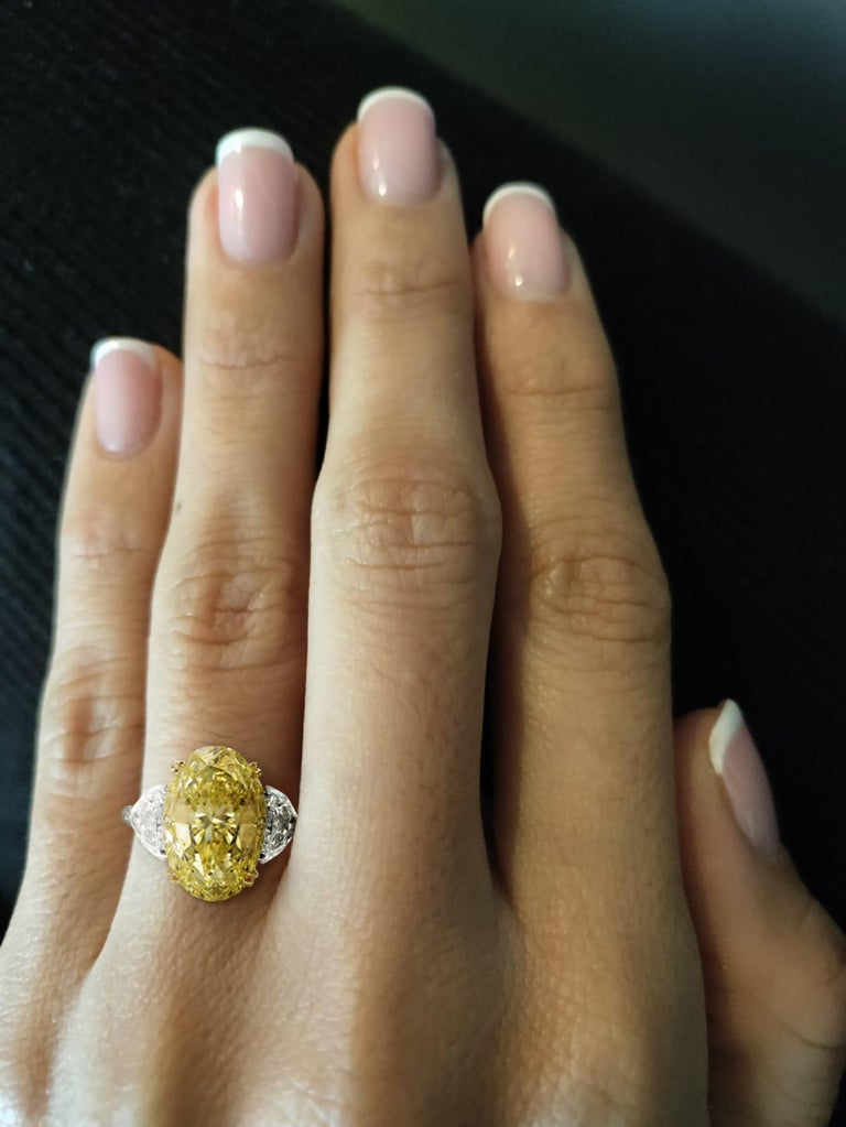 This important and fancy yellow oval diamond is offered by Antinori Fine Jewels It is custom set in a handcrafted in 18 karat white and yellow gold 3 stone ring consisting of an oval cut fancy light yellow diamond with high intensity has a very