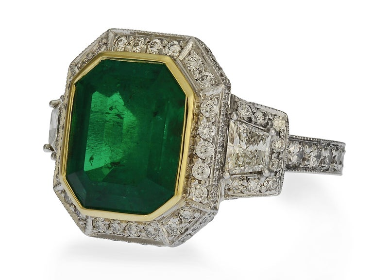 This one-of-a-kind Colombian emerald cocktail ring is custom made in 18 karat white gold with an 18 karat yellow gold bezel. The centerpiece is an emerald cut Colombian emerald, graded by GIA as natural & transparent, with minimal (F1) treatment.