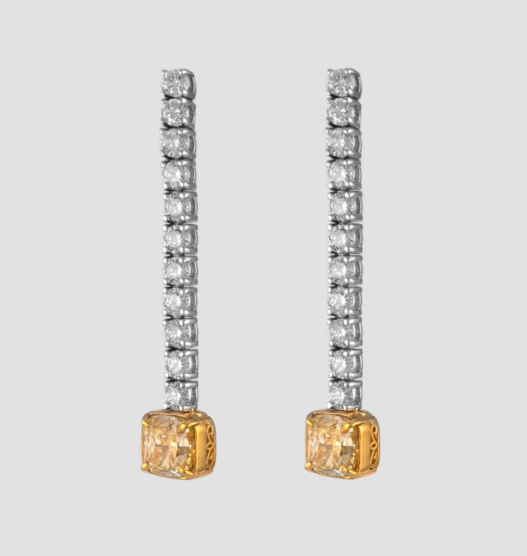 """Stunning dangling diamond earring, each center stone GIA certified with """"fancy yellow look"""" Two matching center cushion diamonds 3.00 carats total. One stone YX color grade and ther other WX color grade. One stone VS1 clarity grade and the other SI1"""