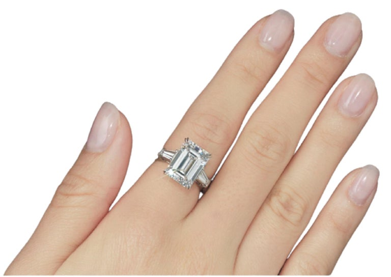 An exquisite emerald cut diamond ring composed by a main stone that weights 5 carats has an excellent proportion polish and symmetry. The side stones are tapered baguettes also very pure and white  The ring is set in solid platinum