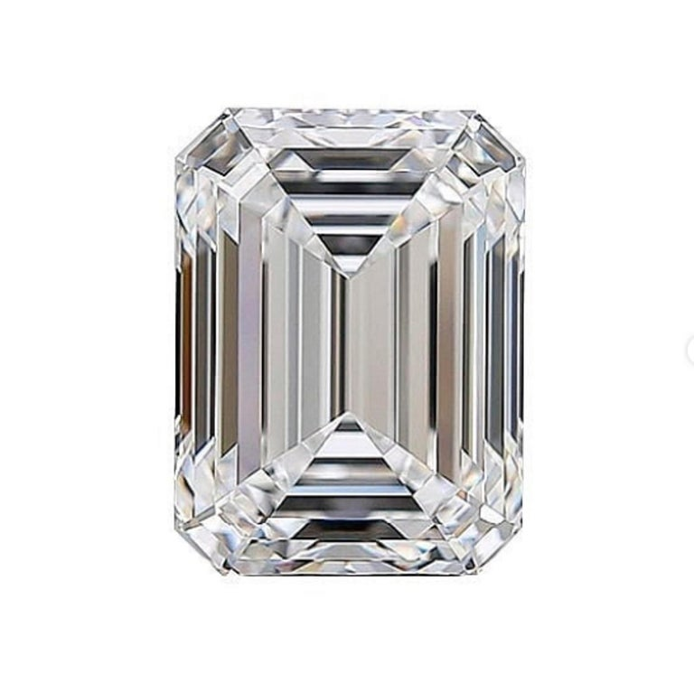 This lovely and rare ring centers on a 3 carat emerald-cut diamond with Internally flawless  clarity. This stone is flanked by two emerald cut diamonds mounted in platinum.   This diamond also has the perfect proportions the ideal emerald cut