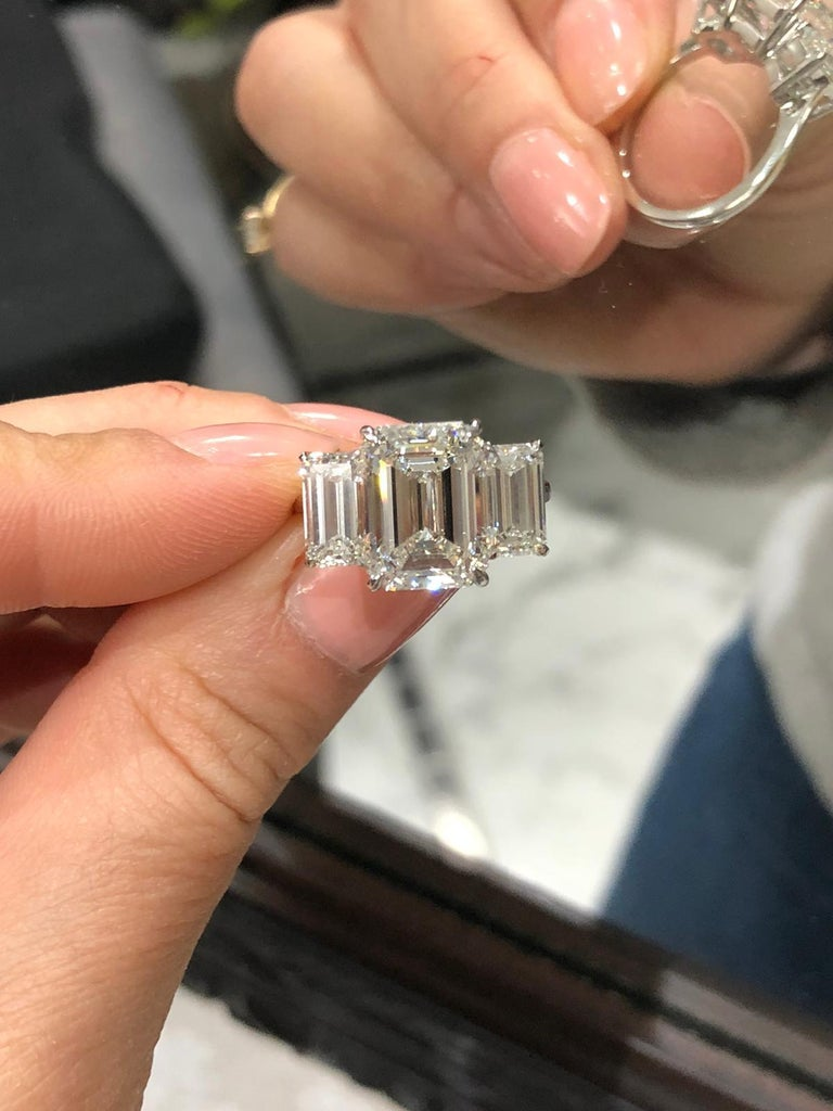 An extraordinary GIA certified three stone 7 carat emerald cut diamond ring. The main stone is a 5 carat I color VS2 Clarity 100% Eye clean stone
